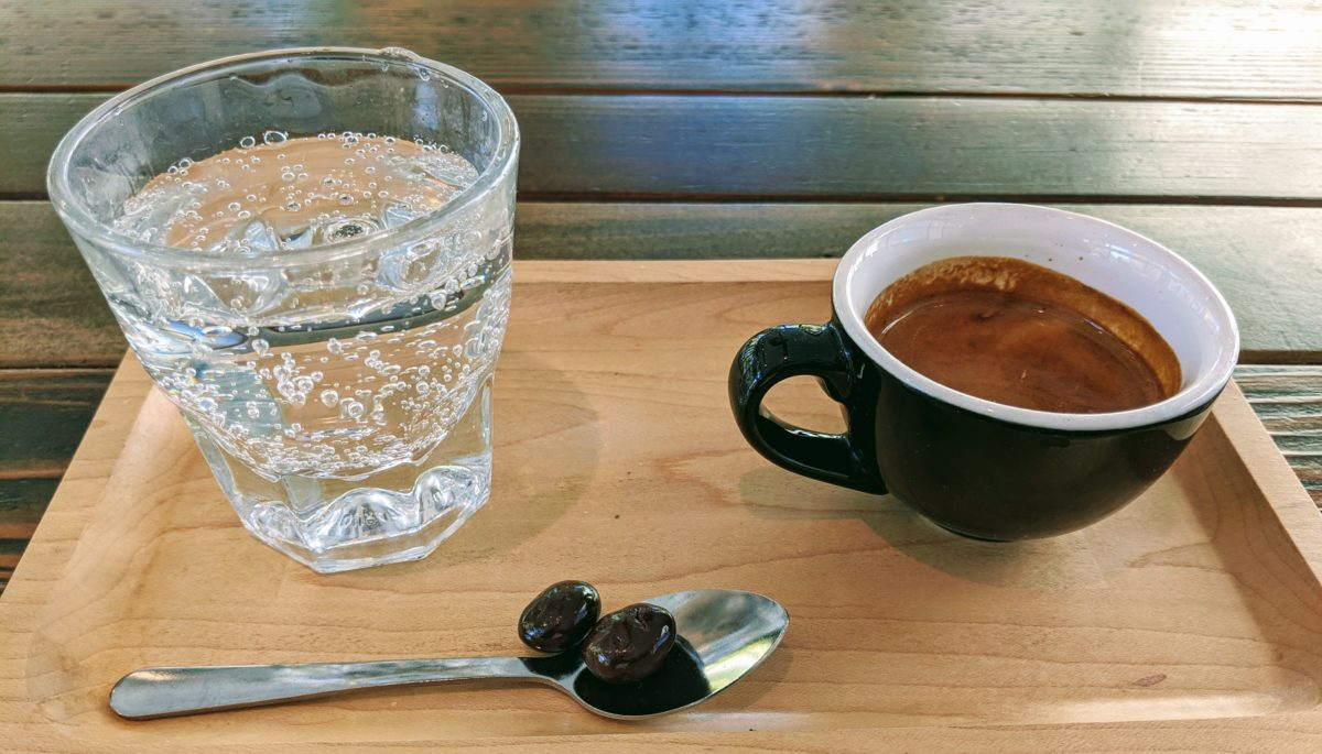 A tray with sparkling water, espresso, and chocolate covered espresso beans.