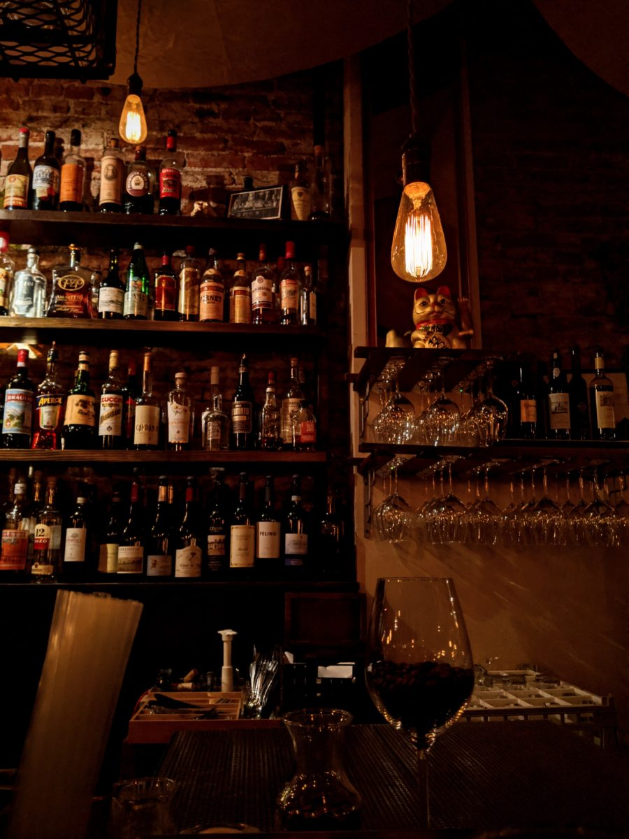 A bar with liquor bottles on a shelf against the wall.